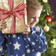 Boy with a giftbox in front of christmas tree — Stock Photo #4840904