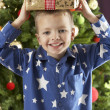 Boy eating cokie in front of christmas tree — Stock Photo