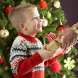 Young Boy Holding Christmas Present In Front Of Christmas Tree — 图库照片