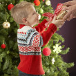 Young Boy Holding Christmas Present In Front Of Christmas Tree — Foto de Stock