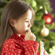 young girl eating star geformten christmas cookie an weihnachtsbaum — Stockfoto
