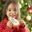 Young Girl Eating Star Shaped Christmas Cookie In Front Of Christmas Tree — Stockfoto