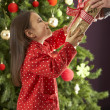 Young Girl Holding Gift In Front Of Christmas Tree - Stok fotoraf