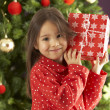 Young Girl Holding Gift In Front Of Christmas Tree - Stockfoto
