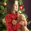 Young Girl Cuddling Teddy Bear In Front Of Christmas Tree - Stock Photo