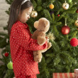 Young Girl Cuddling Teddy Bear In Front Of Christmas Tree — Stock Photo