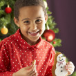 Young Boy Eating Cookie In Front Of Christmas Tree — ストック写真