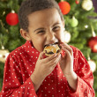Young Boy Eating Cookie In Front Of Christmas Tree — Stockfoto