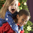 Two Young Children Having Fun In Front Of Christmas Tree — Stockfoto