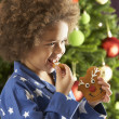 Royalty-Free Stock Photo: Young Boy Eating Cookie In Front Of Christmas Tree