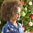 Young Boy Holding Wrapped Present In Front Of Christmas Tree — Stock Photo