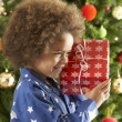 Young Boy Holding Wrapped Present In Front Of Christmas Tree — Stockfoto