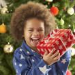 Young Boy Holding Wrapped Present In Front Of Christmas Tree — ストック写真