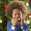 Young Boy Crossing Fingers In Front Of Christmas Tree - Stok fotoğraf