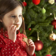 Young Girl Eating Cookie In Front Of Christmas Tree — Stockfoto