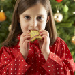 Young Girl Eating Reindeer Shaped Christmas Cookie  — Stockfoto