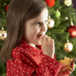 Young Girl Eating Reindeer Shaped Christmas Cookie  — Photo