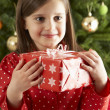 Young Girl Holding Gift In Front Of Christmas Tree - Lizenzfreies Foto
