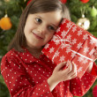 Royalty-Free Stock Photo: Young Girl Holding Gift In Front Of Christmas Tree