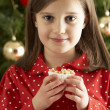Stock Photo: Young Girl Eating Reindeer Shaped Christmas Cookie