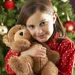 Little girl holding a teddy bear in her hand — Stock Photo