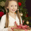 Young Girl Holding Christmas Present In Front Of Christmas Tree - Foto Stock