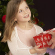 Young Girl Holding Christmas Present In Front Of Christmas Tree - Zdjęcie stockowe