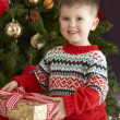 Young Boy Holding Wrapped Present In Front Of Christmas Tree - Lizenzfreies Foto