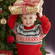 Young Boy Holding Christmas Present In Front Of Christmas - Lizenzfreies Foto