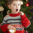 Young Boy Eating Cookie In Front Of Christmas Tree - Stock Photo