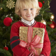 Young Boy Holding Christmas Present In Front Of Christmas — Stockfoto
