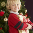 Young Boy Holding Gift In Front Of Christmas Tree — Stock Photo #4841009