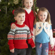 Group Of Young Children With Presents In Front Of Christmas - Lizenzfreies Foto
