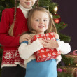 Two Young Girls With Presents In Front Of Christmas Tree - Lizenzfreies Foto