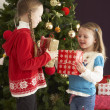 Two Young Girls With Presents In Front Of Christmas Tree - ストック写真