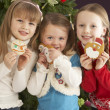 Girls Eating Cookies In Front Of Christmas Tree — Stockfoto