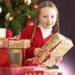 Young Girl Holding Christmas Present In Front Of Christmas Tree - 图库照片