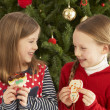 Stock Photo: Girls Eating Cookies In Front Of Christmas Tree