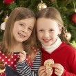 Girls Eating Cookies In Front Of Christmas Tree — Stock Photo