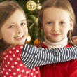 Two Young Girls Hugging In Front Of Christmas Tree — Stockfoto