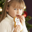 Young Girl Eating Cookie In Front Of Christmas Tree — Photo
