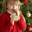 Ygirl christmas celeoung Girl Eating Cookie In Front Of Christmas Tree — 图库照片