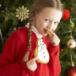 Ygirl christmas celeoung Girl Eating Cookie In Front Of Christmas Tree — Stock fotografie