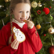 Ygirl christmas celeoung Girl Eating Cookie In Front Of Christmas Tree — Stock Photo