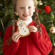 Ygirl christmas celeoung Girl Eating Cookie In Front Of Christmas Tree — Stockfoto