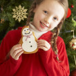 Ygirl christmas celeoung Girl Eating Cookie In Front Of Christmas Tree — Stockfoto #4841035