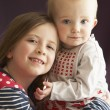 Studio Shot Of Two Sisters Hugging - Foto Stock