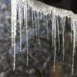 The icicles which are hanging down from a roof at home - Stock Photo