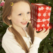 Young Girl Holding Christmas Present In Front Of Christmas Tree - Lizenzfreies Foto