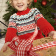 Young Boy Holding Gift In Front Of Christmas Tree — Stockfoto